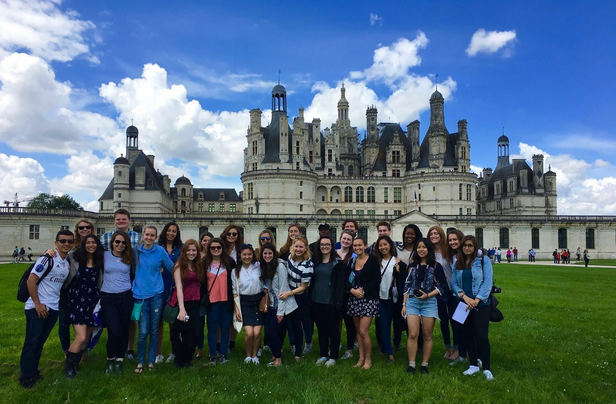 Group of students posing in front of French castle.